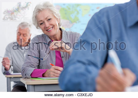 Adult students taking test in college during evening class - Stock Photo