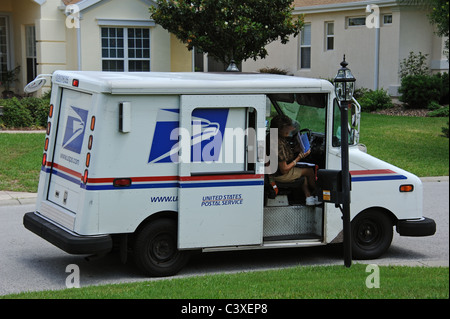 United States Postal Service van on a residential complex Florida USA Mail lady collecting the mail from the mailbox - Stock Photo