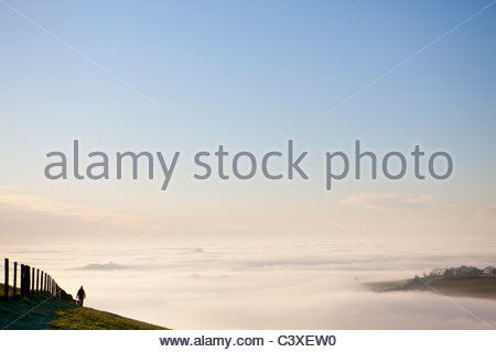 Person walking on hill over fog covered valley - Stock Photo