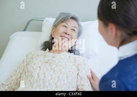 Senior woman lying in bed talking to nurse, Kanagawa Prefecture, Honshu, Japan - Stock Photo