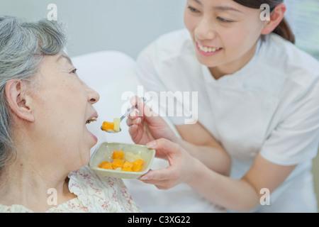 Nurse helping up a senior woman eat in bed, Kanagawa Prefecture, Honshu, Japan - Stock Photo