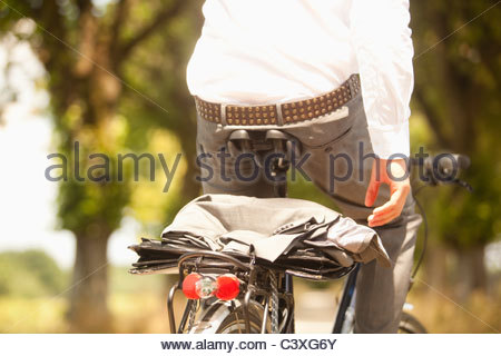 Close-up of coat and briefcase on back of young businessman's bicycle - Stock Photo