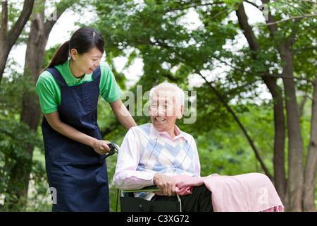 Healthcare worker pushing senior man in wheelchair, Tokyo Prefecture, Honshu, Japan - Stock Photo