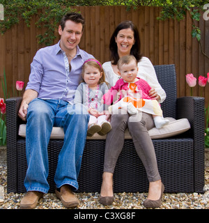 Square family portrait of an attractive husband and wife with their two young daughters sitting in a garden. - Stock Photo
