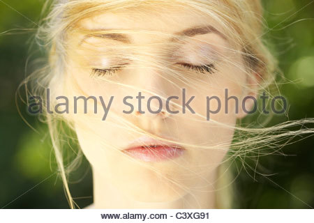 Close-up portrait of young woman with hair in her face - Stock Photo