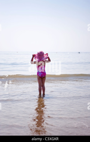 Vertical portrait of a little girl jumping the waves on the beach on a sunny day. - Stock Photo
