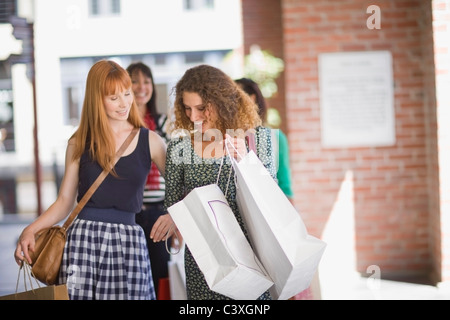 Girlfriends on shopping tour looking in bags - Stock Photo