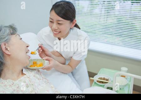 Nurse helping senior woman eat food, Kanagawa Prefecture, Honshu, Japan - Stock Photo
