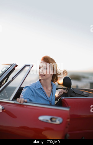 Red haired girl sittin in red car - Stock Photo