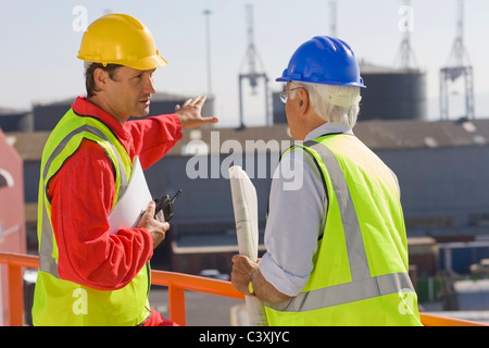 Two harbour workers talking about work - Stock Photo
