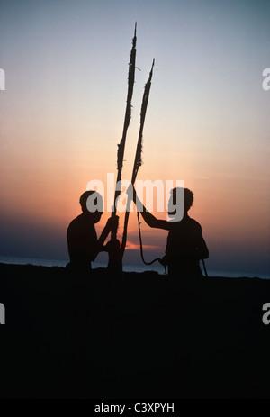 El Molo Warriors and Hunters talking, silhouetted by Lake Turkana after a Hippopotamus Hunt. Lake Turkana - Kenya. - Stock Photo
