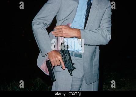 Israeli Secret Service agent draws an uzi pistol from his shoulder holster. Israel. - Stock Photo