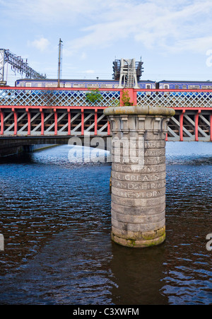 Train crossing the Second Caledonian Railway Bridge over the River Clyde in central Glasgow. Granite pier of 1st - Stock Photo