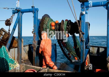New England fisherman hauling in the dragger net on his boat. Stellwagon Bank, New England, Atlantic Ocean. - Stock Photo