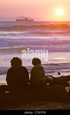 friends and lovers sit and watch freighter ship sail into the sunset at ocean beach San Francisco California USA - Stock Photo