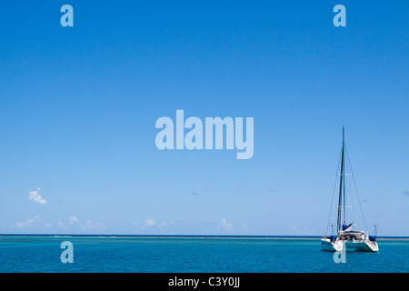 Sparse image of catamaran sailboat moored in turquoise water and blue sky in Caribbean Sea