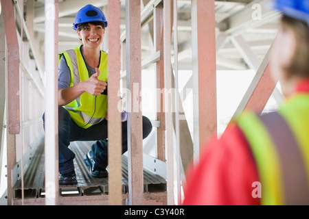 Female architect talkiing to a builder - Stock Photo