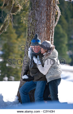 Couple hugging near tree outdoors in snow - Stock Photo