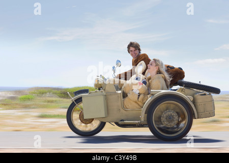 Disguised couple on motorbike - Stock Photo