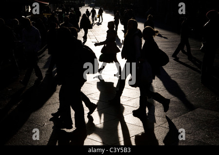 People shopping on a paved city street casting long shadows - Stock Photo