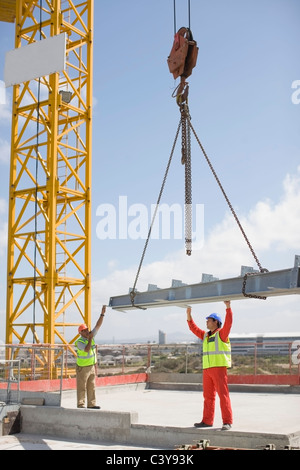 Crane and workers on construction site - Stock Photo