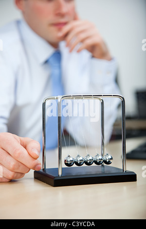 Office worker playing with newtons cradle - Stock Photo