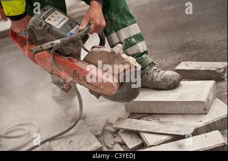 Dirty noisy dusty work; a man using an angle grinder to cut a paving stone, UK - Stock Photo