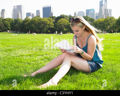 Woman reading a letter in central park - Stock Photo