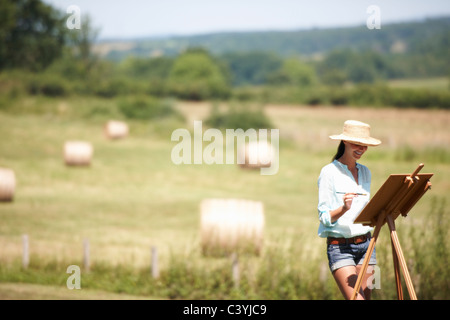 Woman painting a picture, outdoors - Stock Photo
