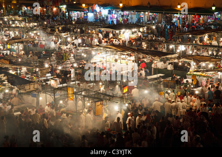 A view of the street restaurants at Djemaa el Fna square at night in the heart of Marrakech, Morocco. - Stock Photo