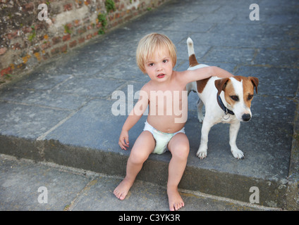 Baby boy playing with a dog - Stock Photo