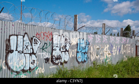 Graffiti on metal fence with barbed wire - Stock Photo