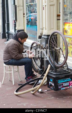 man sitting repairing bicycle on street - Stock Photo