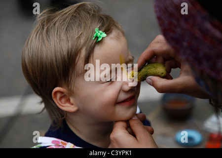 Young German girl being painted in an art street fair in Leipzig Saxony Eastern Germany - Stock Photo
