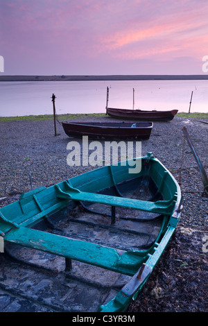 Boats at low tide on the shore of The Fleet lagoon, Chesil Beach, Dorset, England. Spring (March) 2011. - Stock Photo