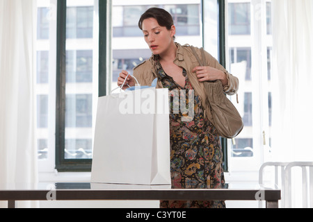woman looking in shopping bag - Stock Photo