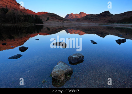 Late autumn light on the icy edges of a calm Blea Tarn in the Lake District of England - Stock Photo