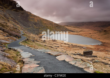 The Miners' Track footpath winding around Llyn Teyrn on the descent from Mount Snowdon, Snowdonia - Stock Photo