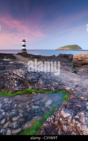 Twilight on the rocky Anglesey coast looking towards Penmon Point Lighthouse and Puffin Island, Anglesey, North - Stock Photo