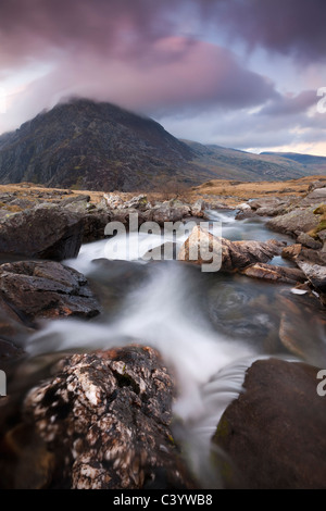 Rocky river in Cwm Idwal leading to Pen yr Ole Wen Mountain at sunset, Snowdonia National Park, Conwy, North Wales - Stock Photo