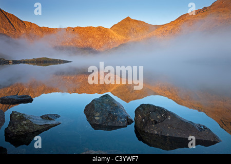 Early morning sunlight illuminates Snowdon from the shores of a misty Llyn Llydaw, Snowdonia National Park, Gwynedd, - Stock Photo
