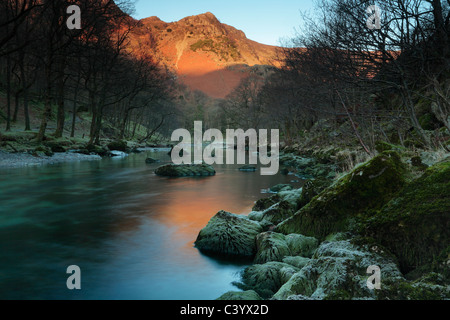Alpenglow on High Crags is reflected in the River Derwent as seen near Rosthwaite in the Lake District of England - Stock Photo