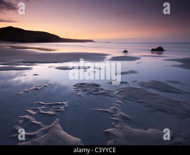 Water pools on the sandy beach at Kennack Sands at sunrise, Lizard Peninsula, Cornwall, England. Spring (May) 2011. - Stock Photo