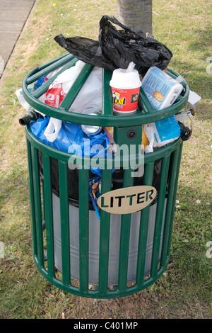 An overflowing litter bin on a post in a public park, Woolwich, East London, UK. - Stock Photo