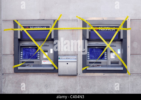NatWest bank branch premises external outdoor atm cash machines two out of order covered in yellow tape London England - Stock Photo
