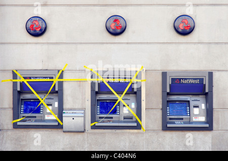 NatWest bank branch premises external outdoor atm cash machines two out of order covered in yellow tape one machine - Stock Photo