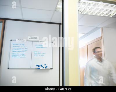 Scientist next to noticeboard - Stock Photo