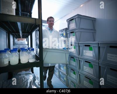 Scientist in laboratory storage fridge - Stock Photo