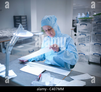 Scientist in clean room with product - Stock Photo