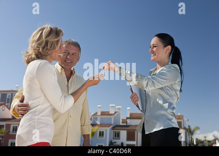 Realestate agent handing keys to couple - Stock Photo